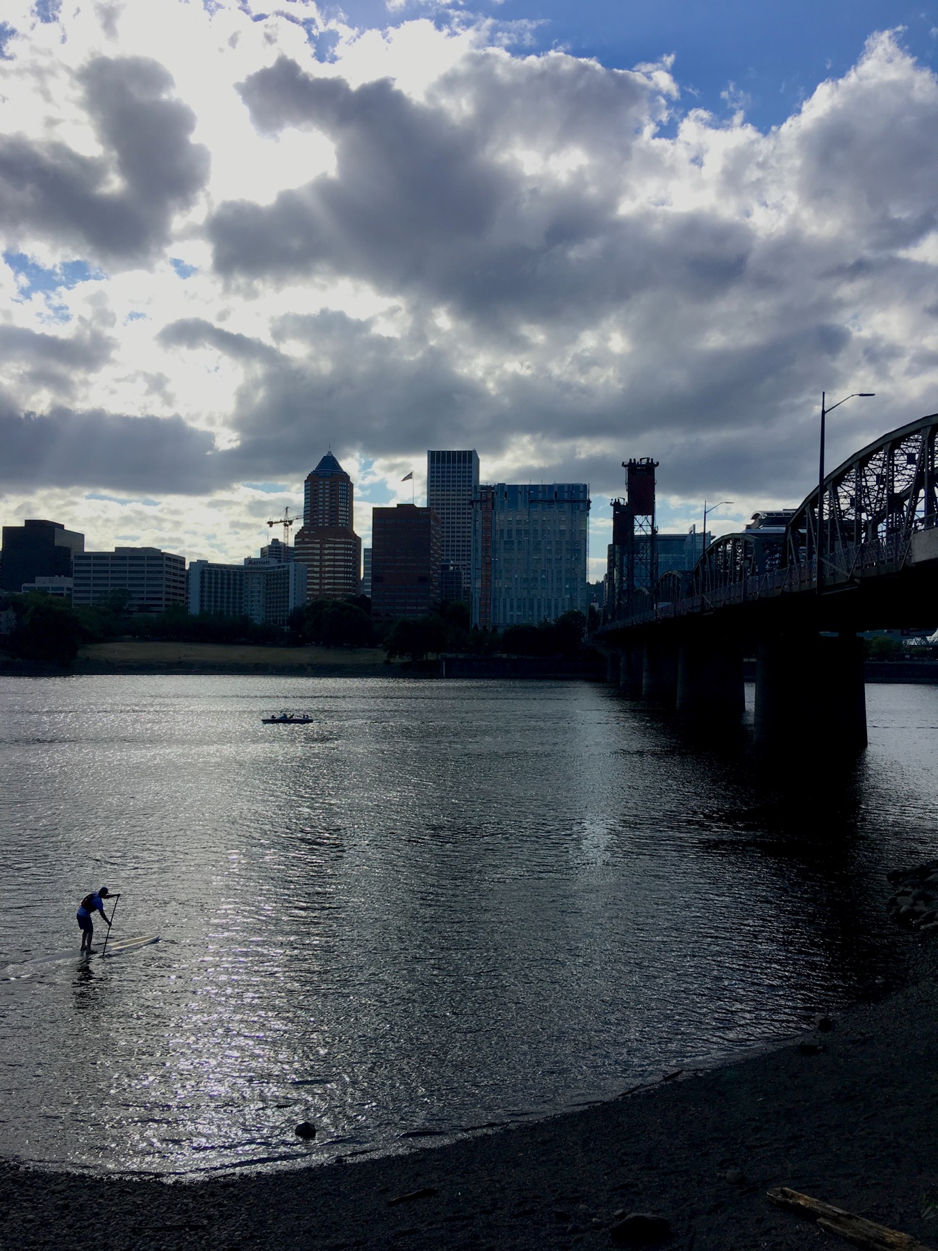 A lone paddleboarder heads underneath Hawthorne bridge in a rare moment of overcast weather.