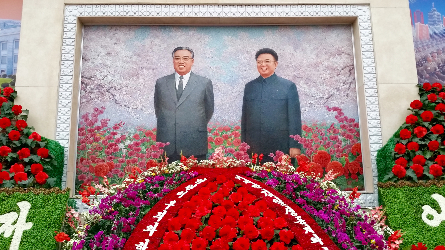 As you enter the exhibit you're greeted by this enormous father-and-son portrait, which I promise you, an image seen time and time again in throughout Pyongyang.