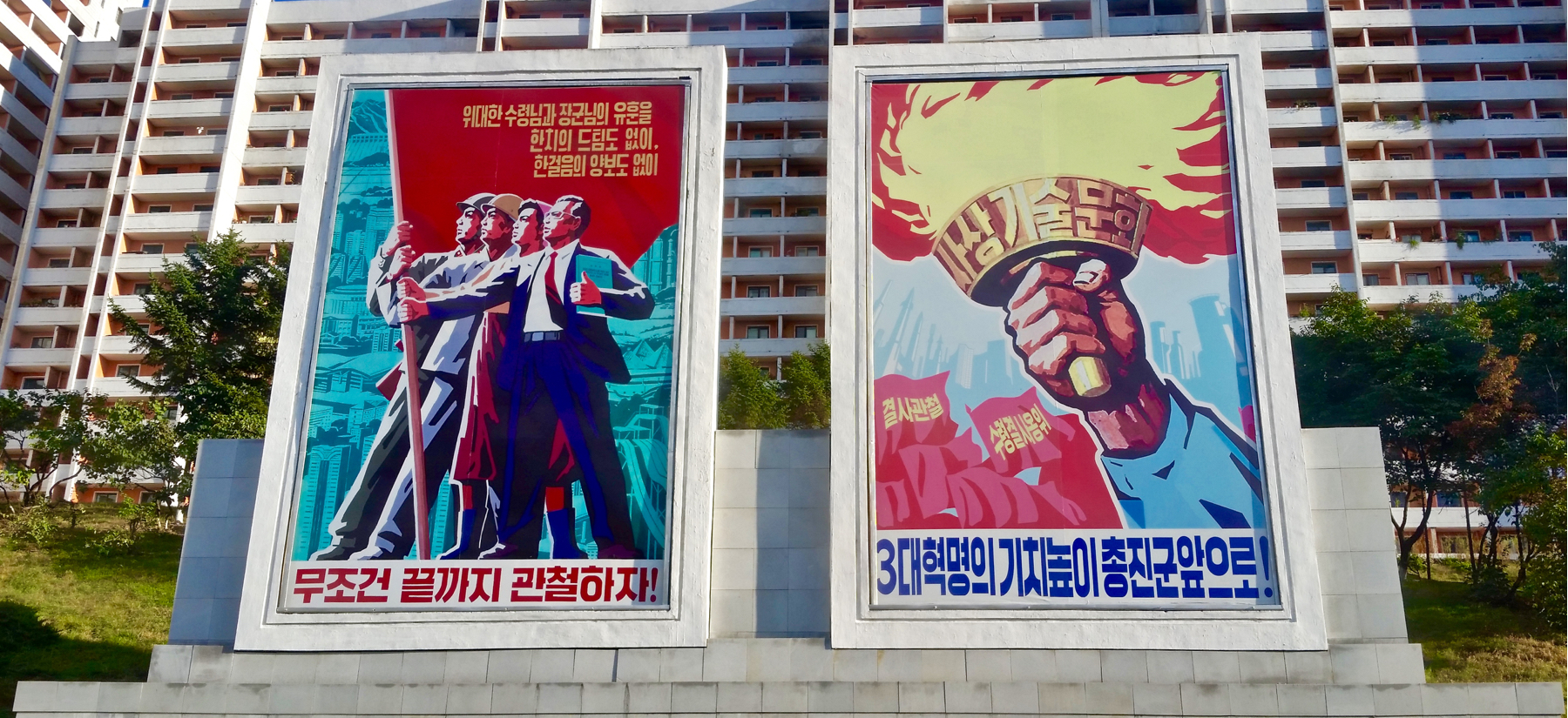 Some roadside propaganda. I tried to translate the captions of each, but it's pretty hard: On the left, 'Succeed unconditionally until the end.' and on the right 'Advance the banner of the three revolutions'?