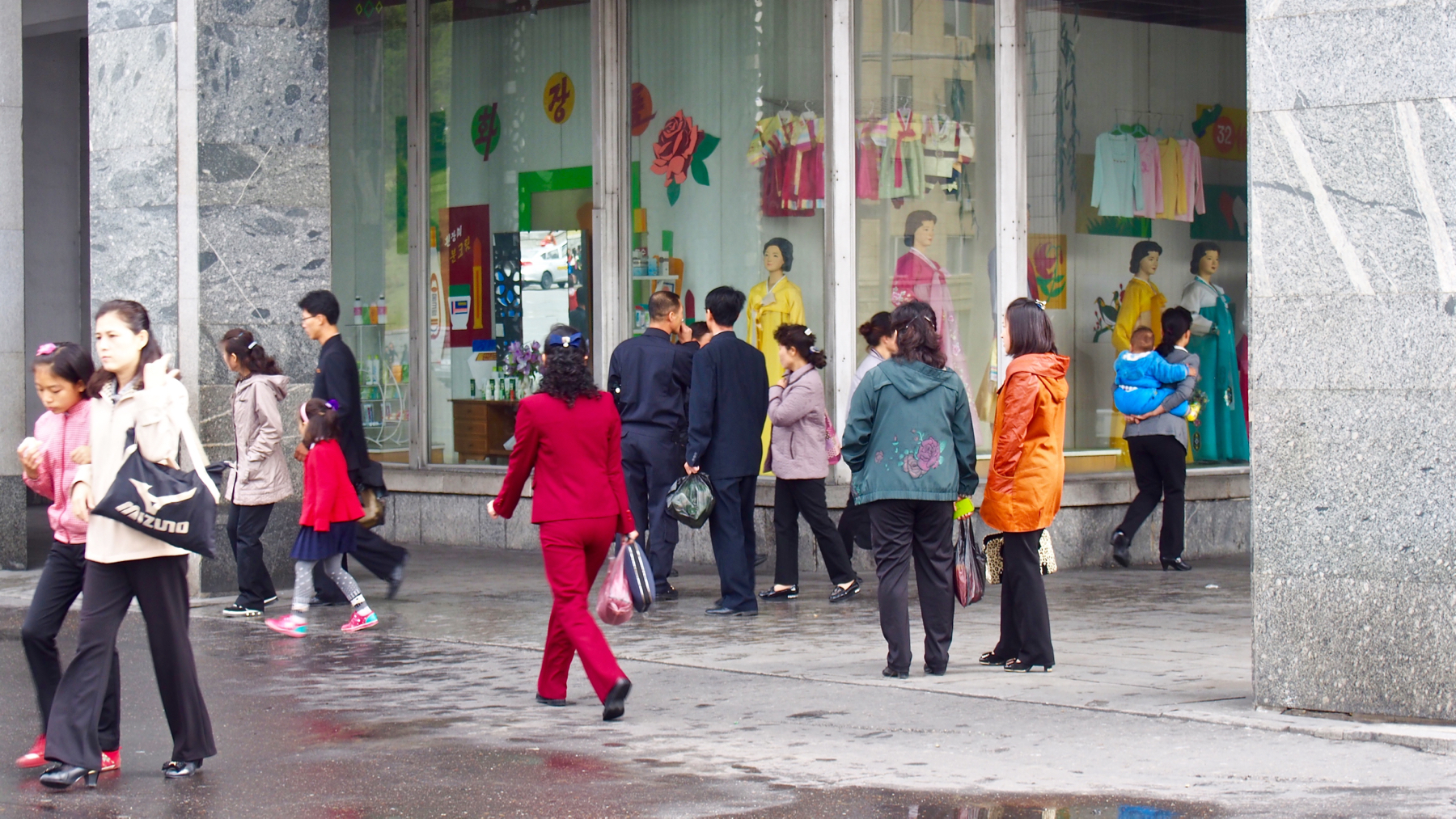 Pyongyangites do some window shopping outside of a department store near Kim Il-sung Square