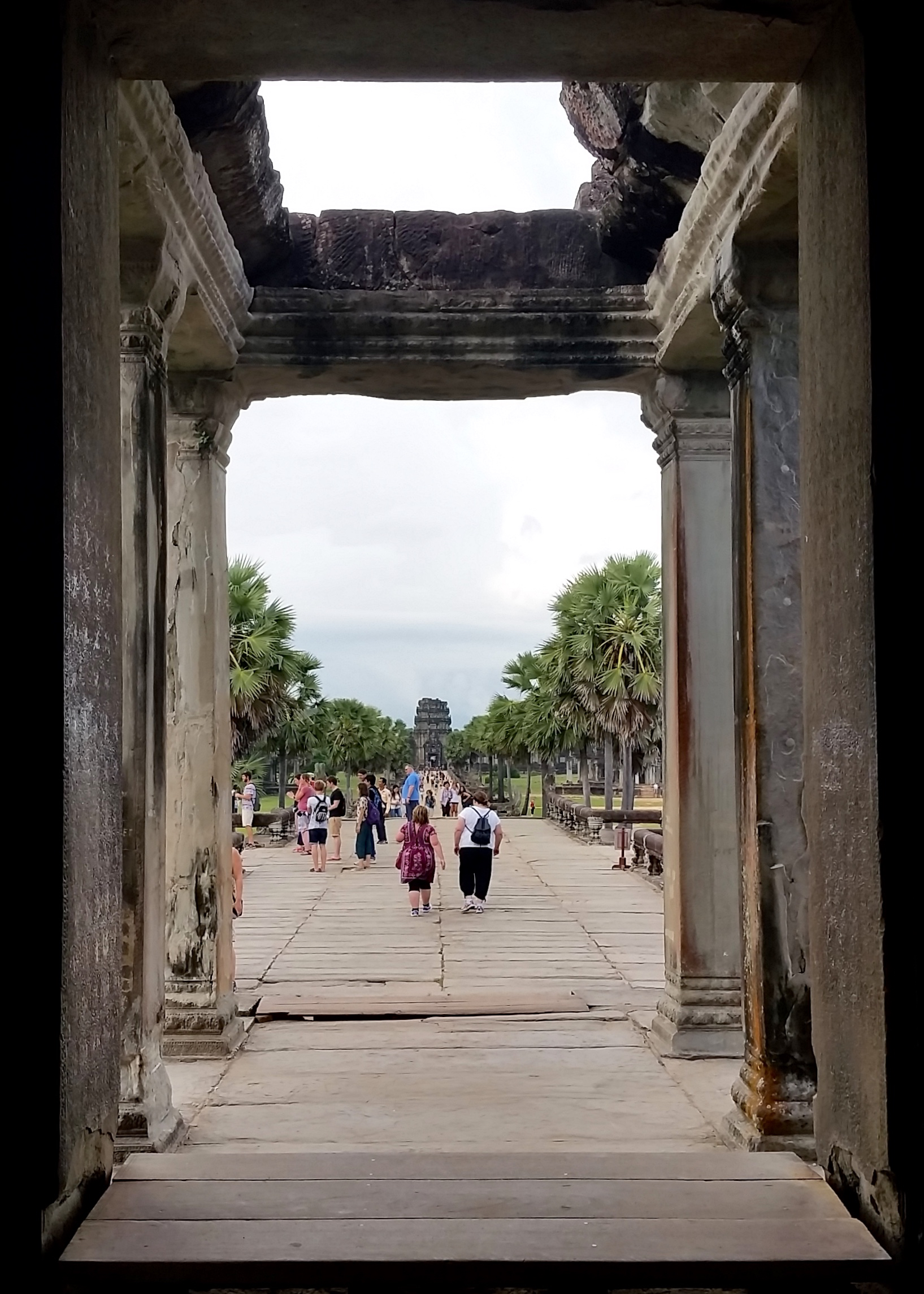 Fellow tourists make their way out of the enormous Angkor Wat temple in Siem Reap, tired from climbing many stairs and admiring many embossed pictures.